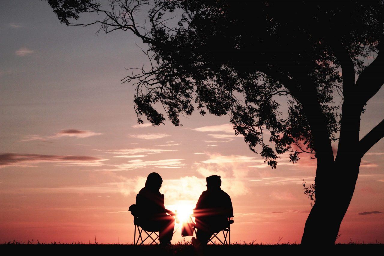 retired couple relaxing under tree during sunset