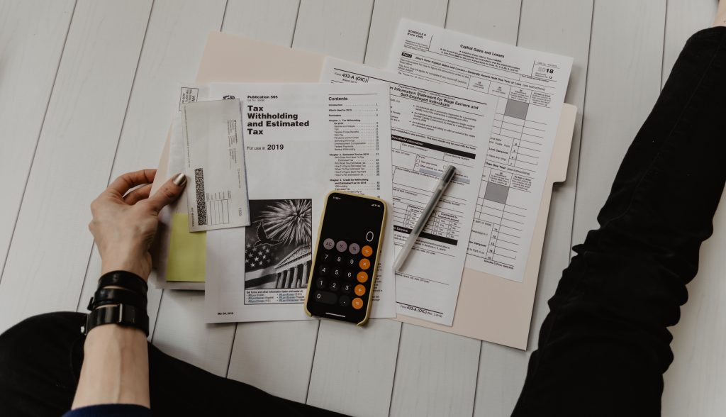 Person sitting on floor trying to do taxes with calculator and tax forms